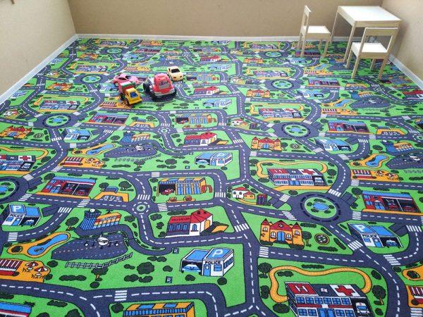 Пътища, цветни сгради и къщи, красиви поляни и цъфнали дръвчета, изобразени на детски килим City Life